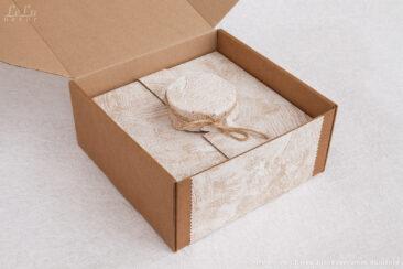 Подсвечник из сосновых шишек и свеча в стакане упакованы в коробку с откидывающейся крышкой и с фигурным ложементом для фиксации всех элементов декоративной композиции.