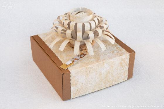 Декоративный подсвечник «Луч солнца» с большой свечой упакованы в оригинальную подарочную коробку с фигурным элементом «Лучистый фонтан» из фактурной плотной бумаги.