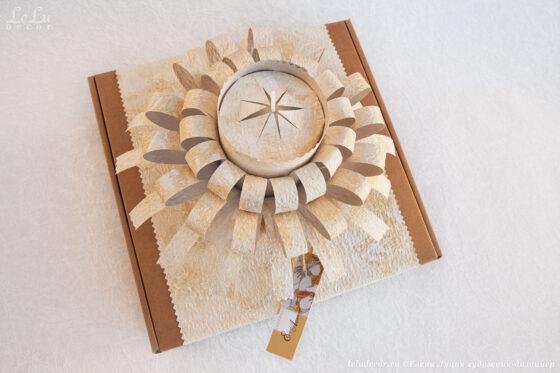 Декоративная композиция – подсвечник «Луч солнца» с большой свечой в подарочной упаковке с фигурным элементом «Лучистый фонтан» из фактурной плотной бумаги.