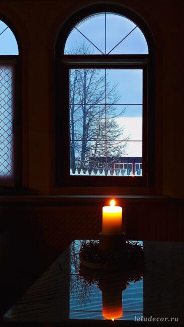 Атмосферное фото декоративного подсвечника «Луч солнца» с зажженной свечой на фоне вечернего окна.